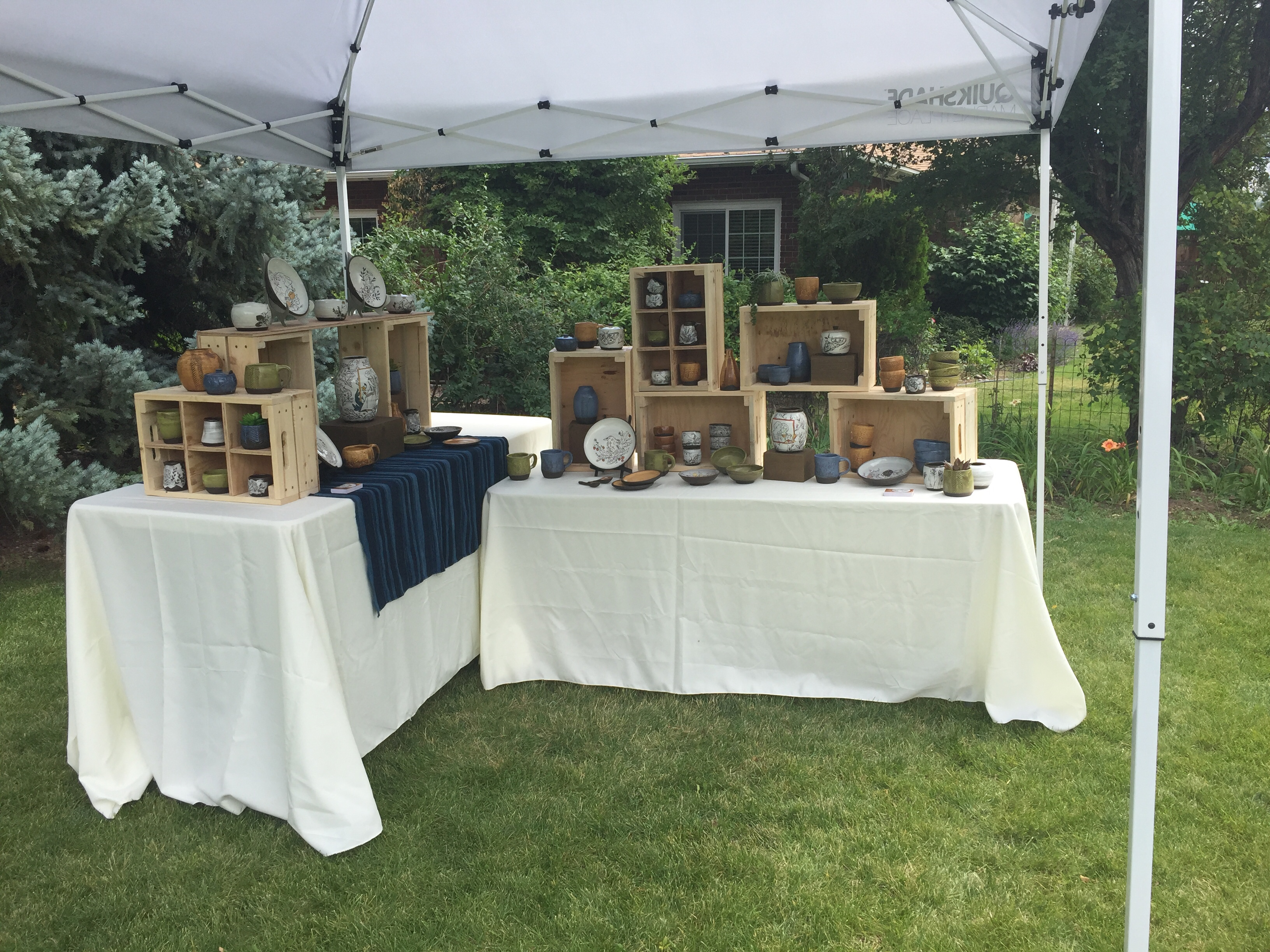 Wide view of the same pottery display - two tables with crates and pottery set in an L-shape on a lawn, under a white canopy.
