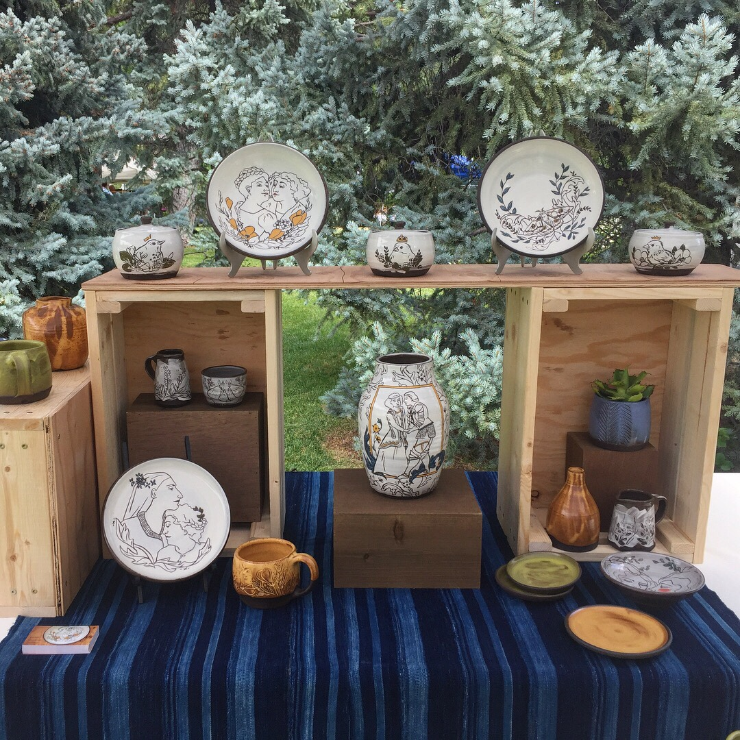 Pottery display using wood crates and small boxes on a blue striped tablecloth. The pottery includes illustrated plates, vases, and jars. There are evergreen trees in the background.