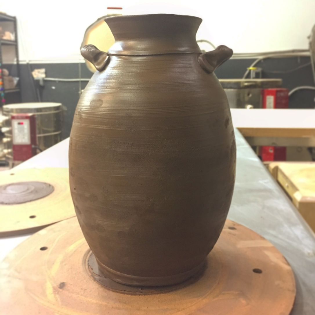 Large clay vase, freshly thrown out of dark brown clay. It's sitting on a throwing bat on a table in a pottery studio.